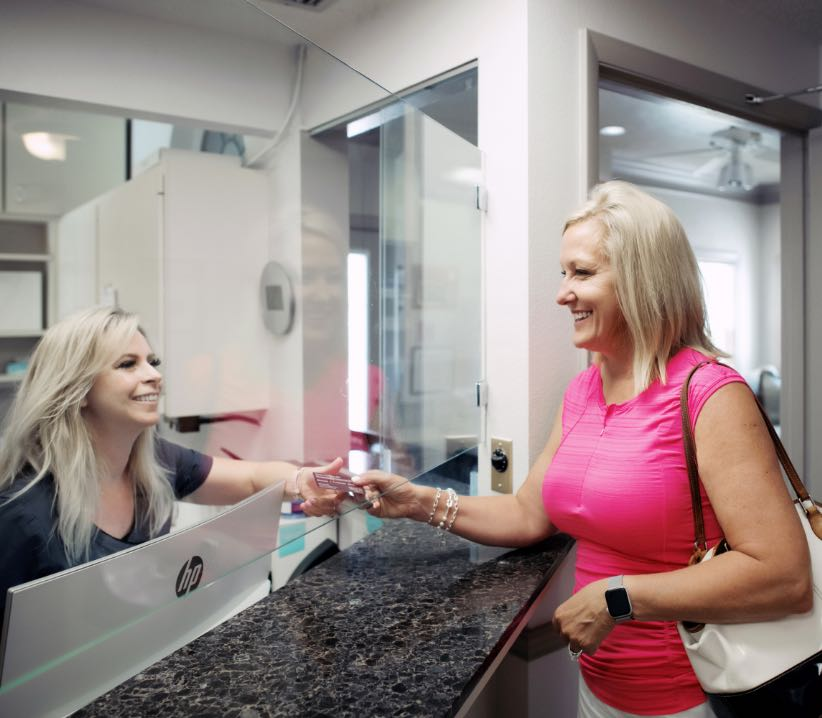 Photo of a patient being helped at the front desk by a Venice team member