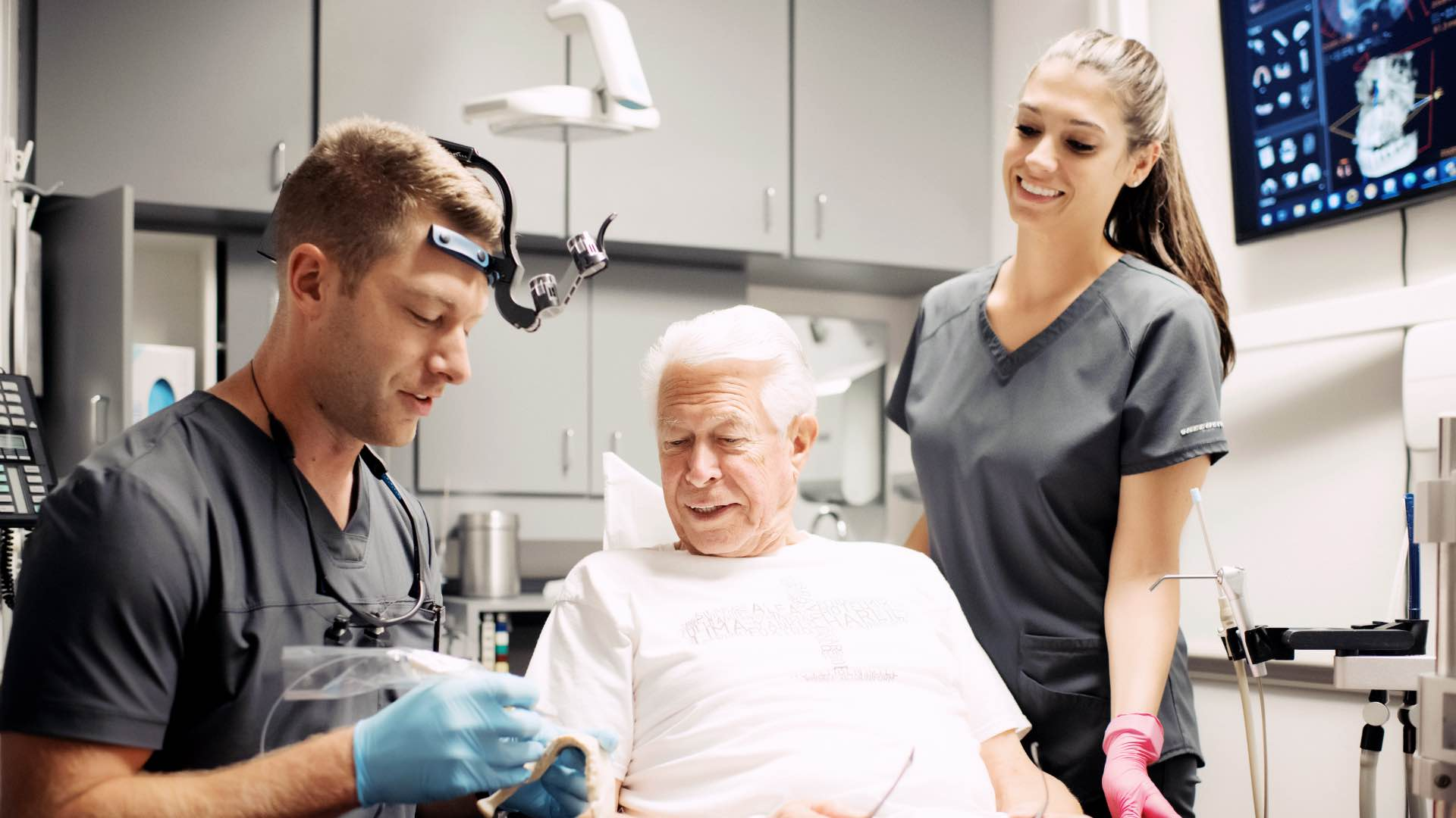 Photo of Dr. Mitchell showing a model to a patient
