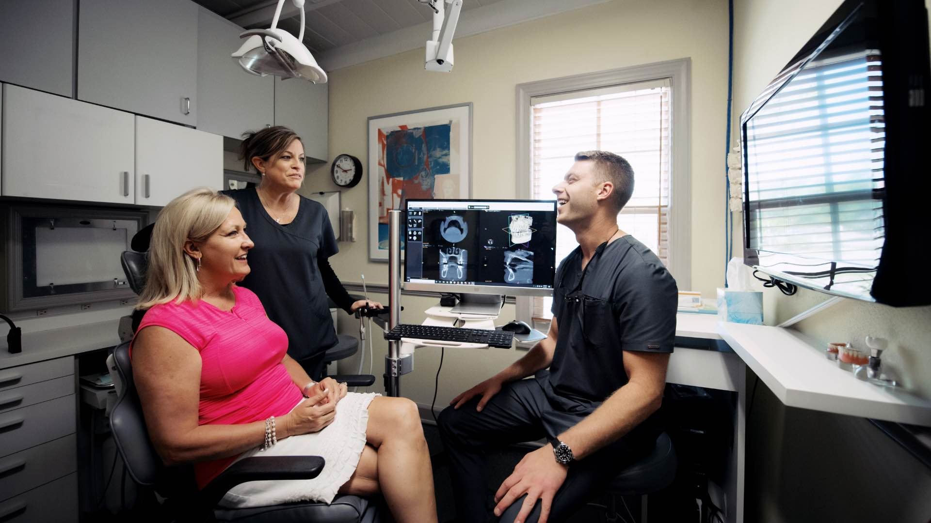 Photo of Dr. Mitchell and a team member reviewing scans with a patient