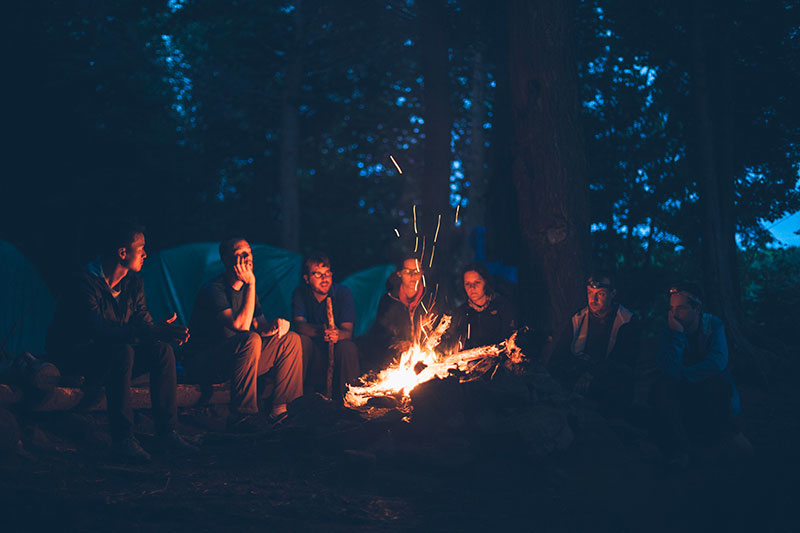 friends hanging out around a fire camp
