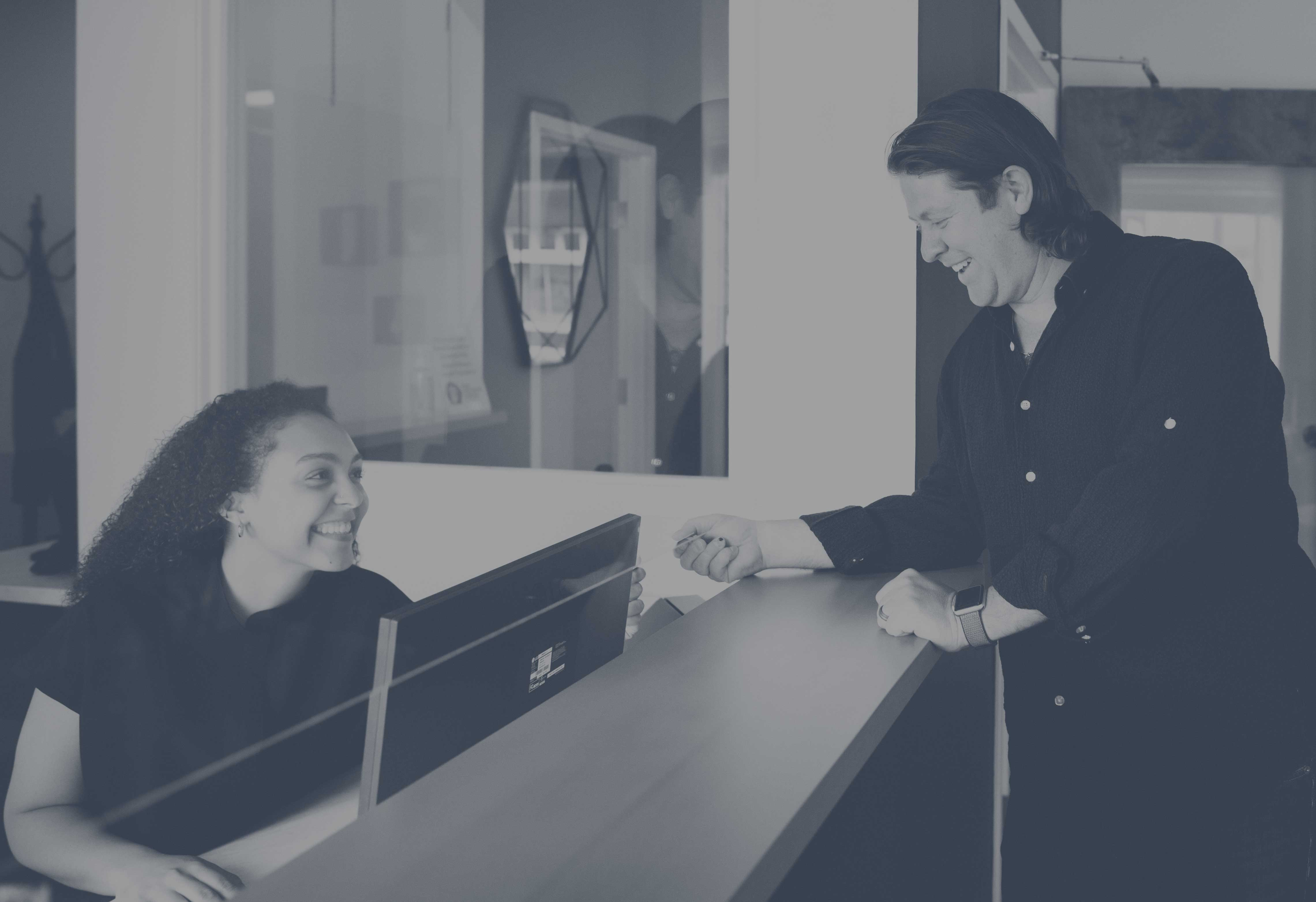 Photo of a patient being helped at the front desk