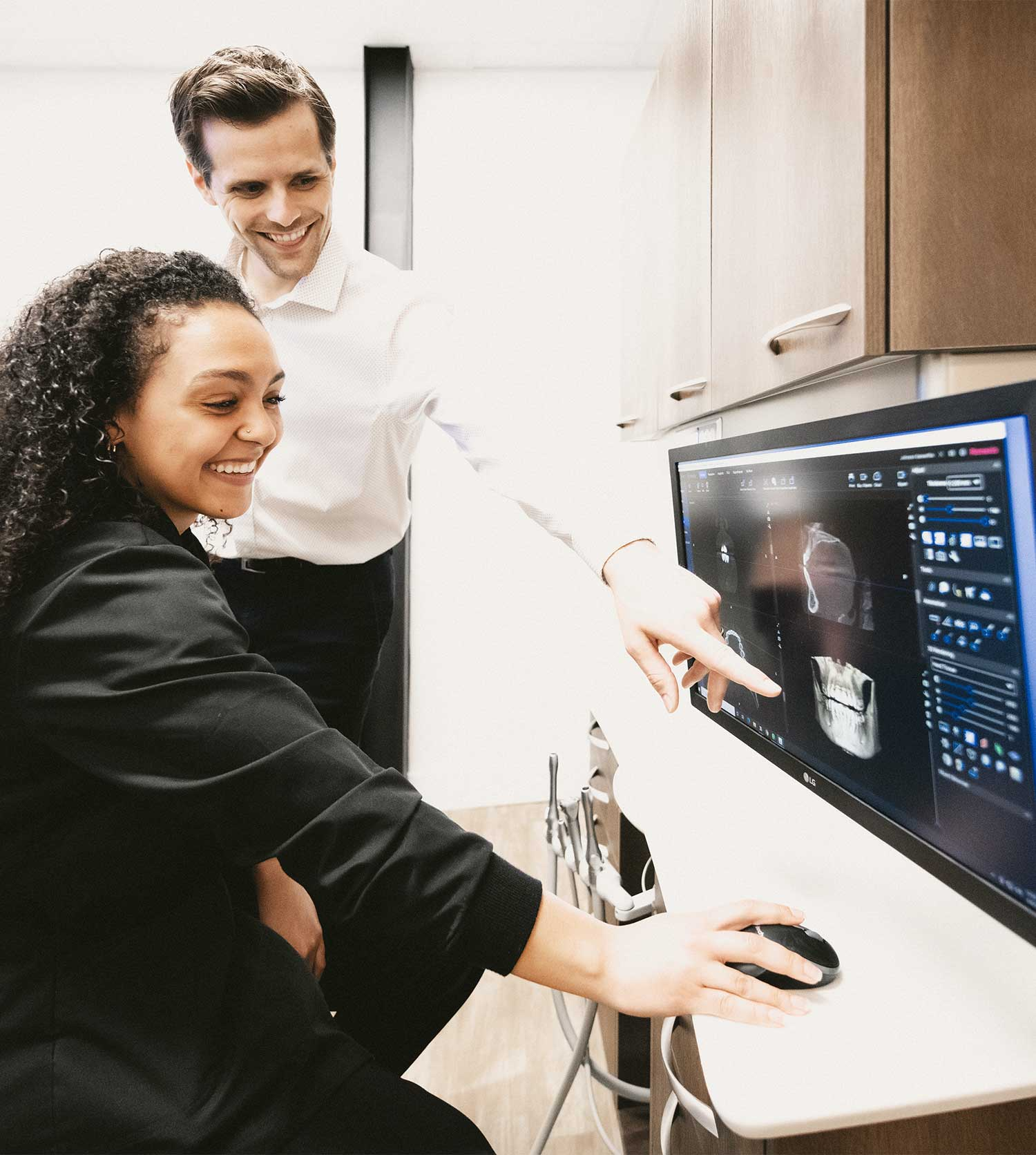 Photo of Dr. Johnson and a team member looking at a digital scan