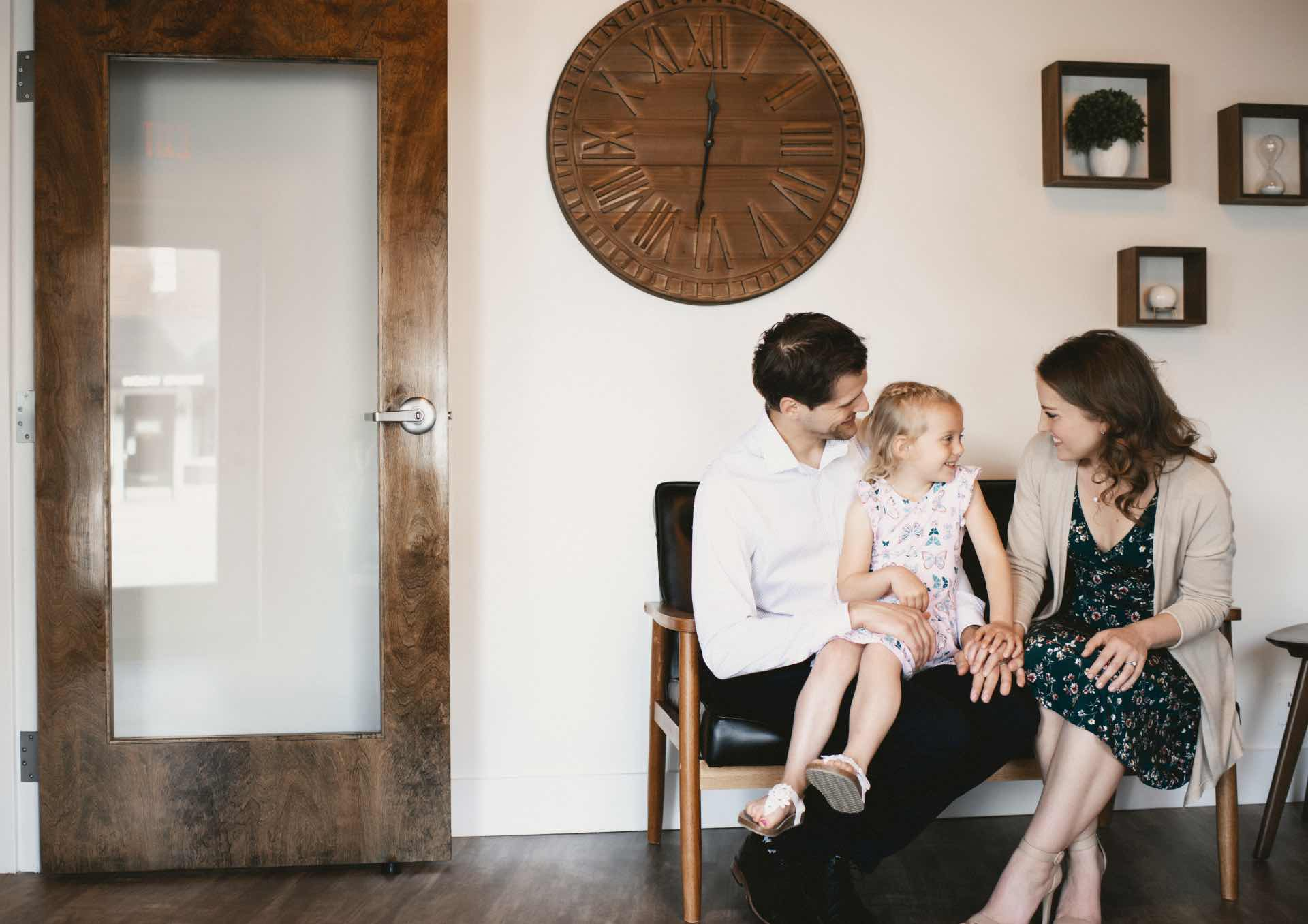 Photo of a little girl with her mother and father in the Neighborhood Dental greeting area