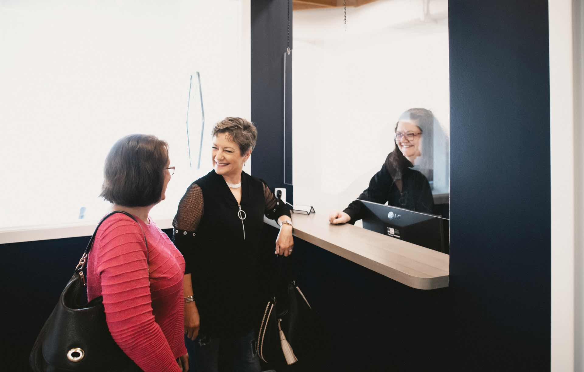 Photo of two patients receiving assistance at the front desk