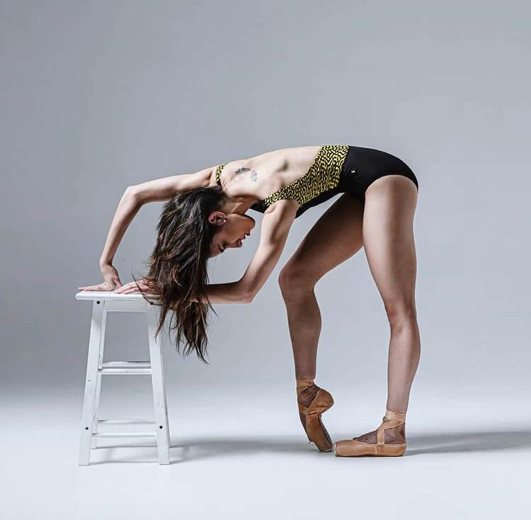 Ballet dancer posing in a black and yellow ballet bodysuit.