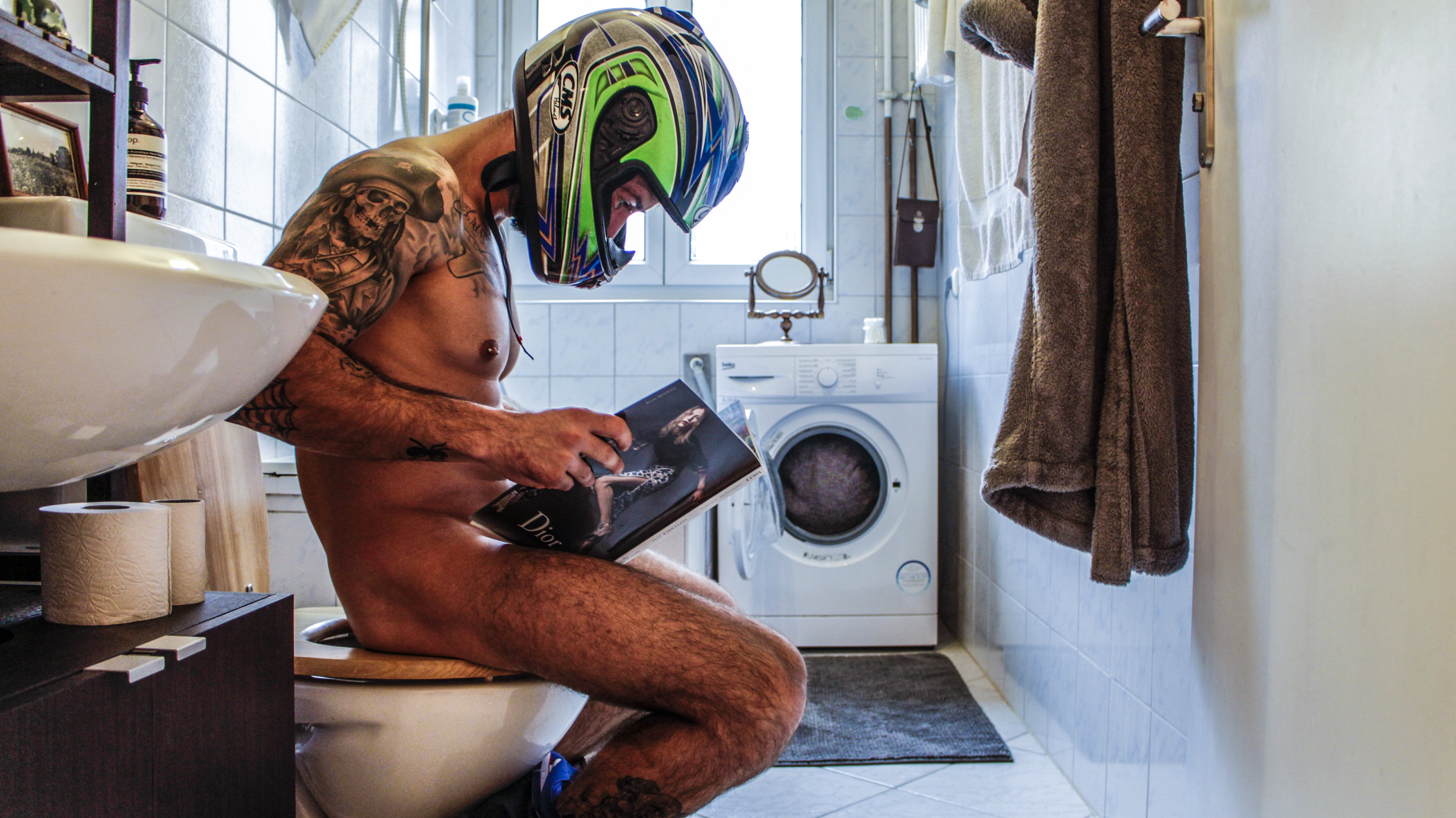 Man sitting on a toilet with the helmet on, photograph of Paco Pennino who won the Beazy Architecture contest