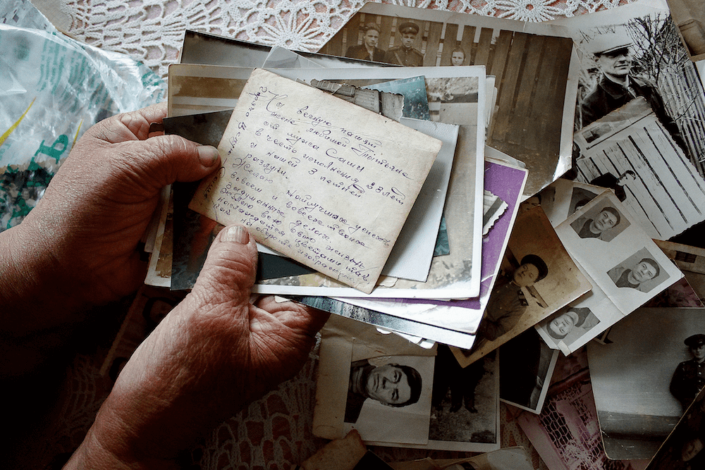 Hands of grand mother with letters and old photos in Belarus by photographer Krystsina Shyla