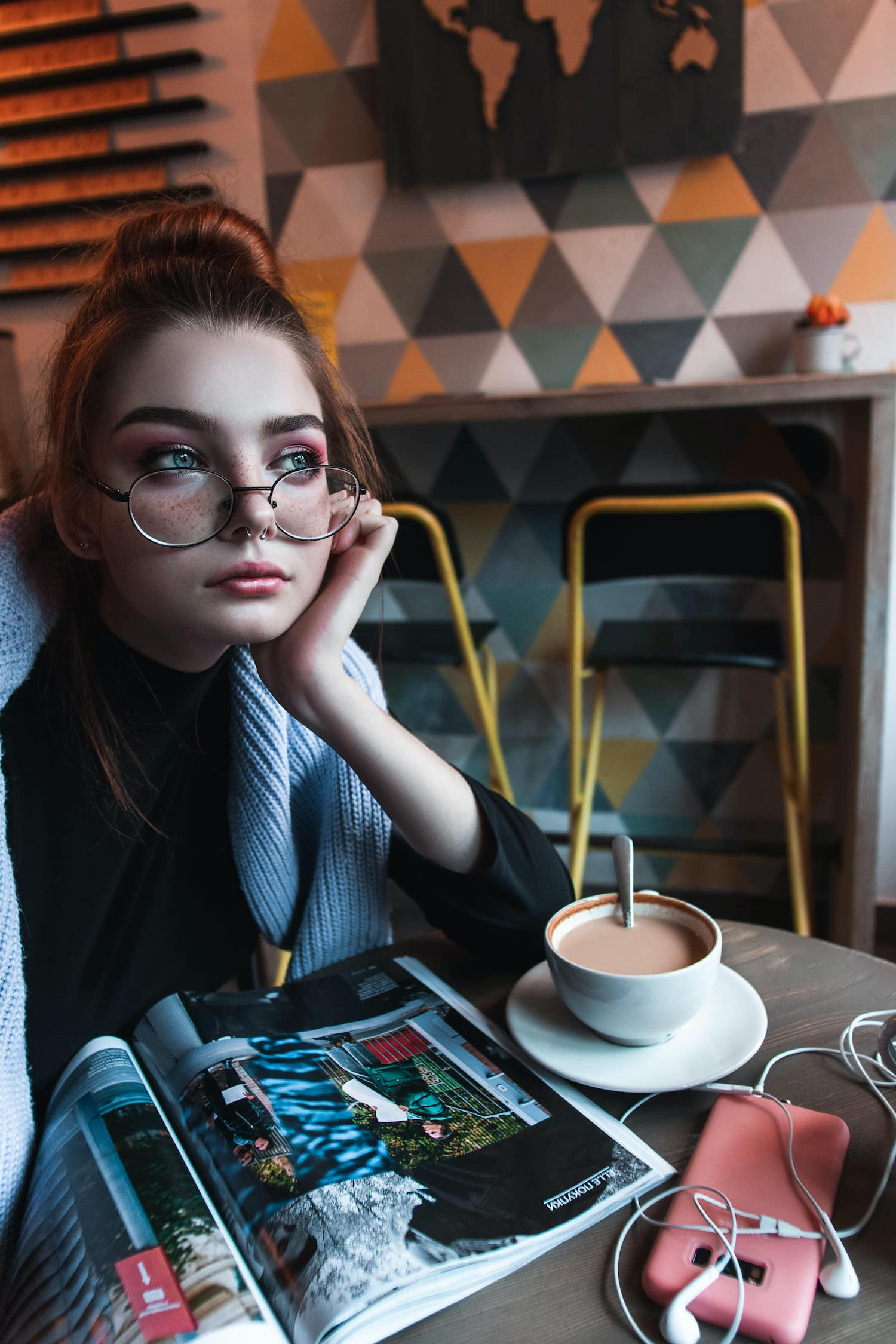 A young girl wearing glasses in a café, drinking a coffee and reading a magazine.