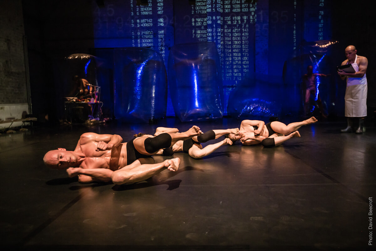 A theatrical performance: three naked men on the floor and a man dressed as a scientist behind them.