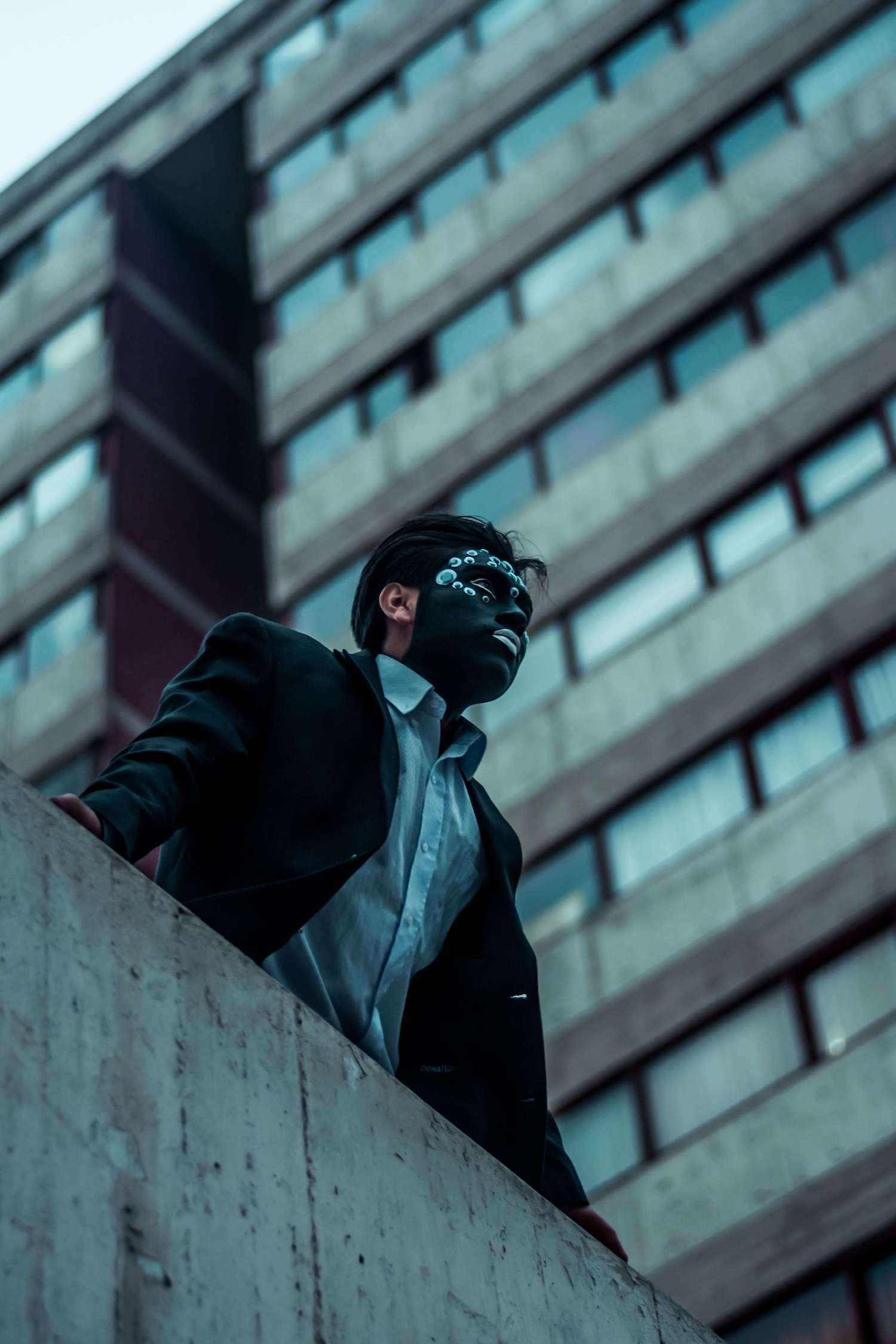 A man wearing a black decorative mask in an industrial area.