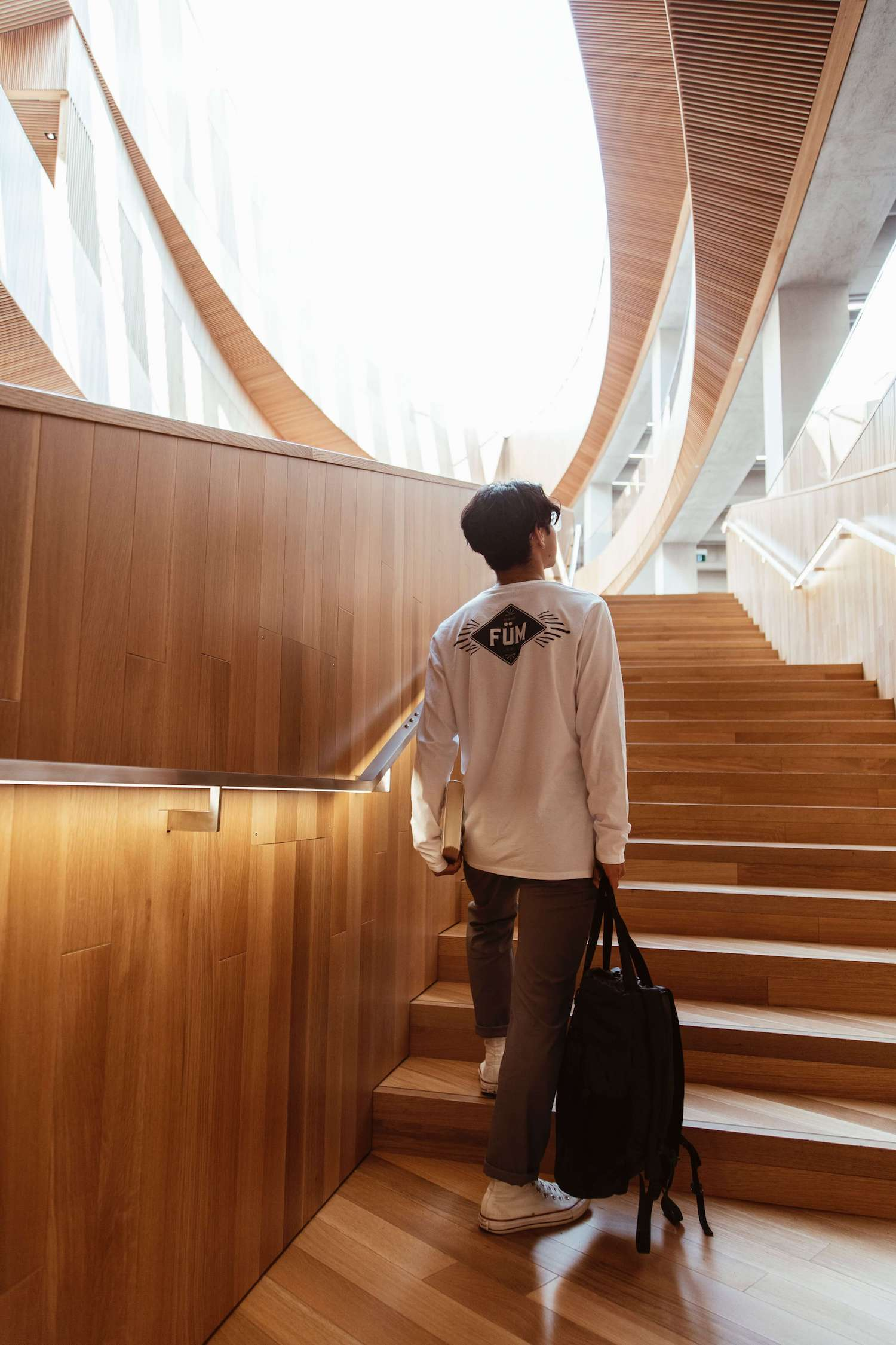 A young man going upstair in a modern designed library.