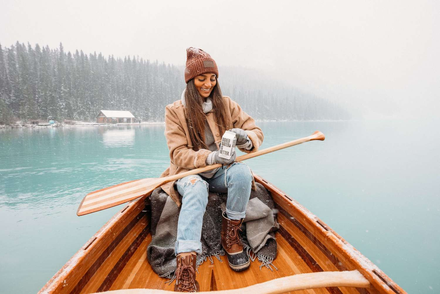 Young woman drinking boxed water in a little boat, snowing.