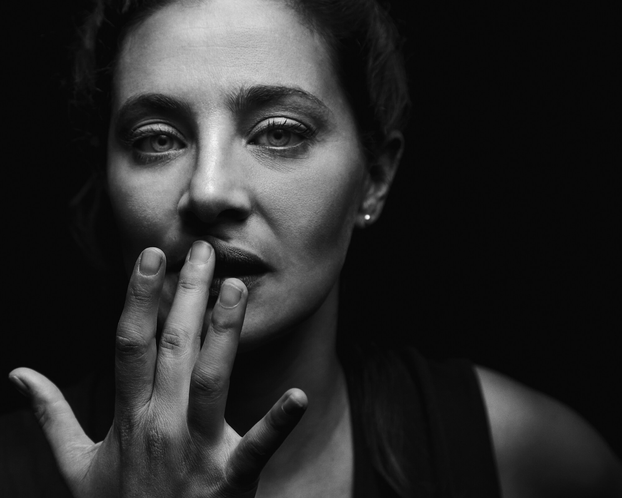 Portrait of Annalisa, black and white, high contrast photo of the model touching her lip. Winning photo of the Beazy December Contest.