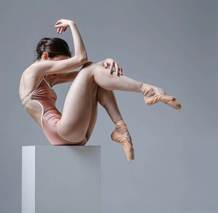 Ballet dancer doing a ballet pose, seated on a stool.