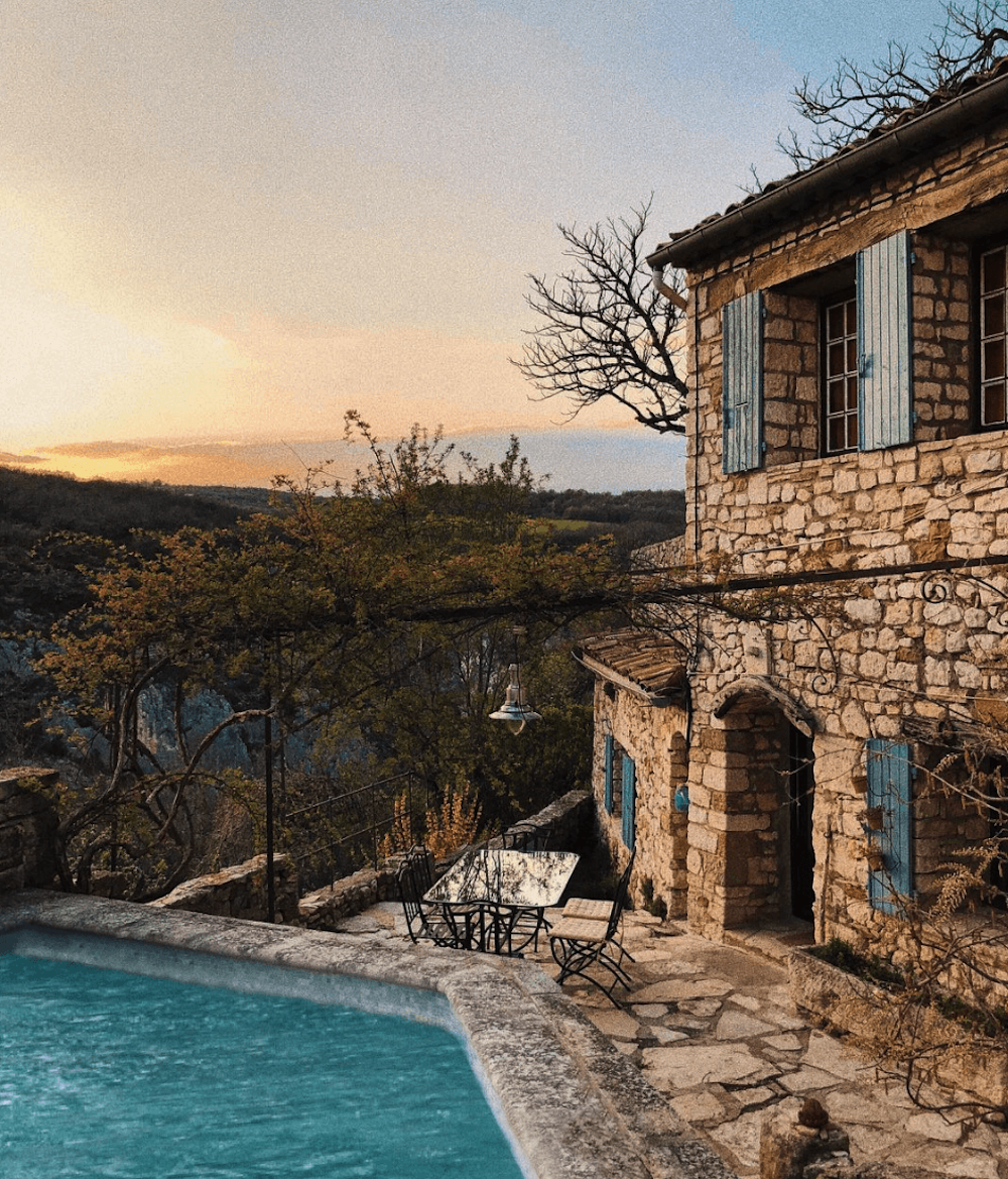 A rural house with swimming pool, during the sunset.