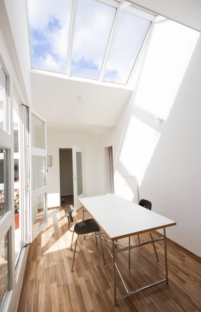 Dining room of a rooftop garden apartment in architect building, available to rent as a film location in Berlin, Germany. Extremely bright for photoshoots