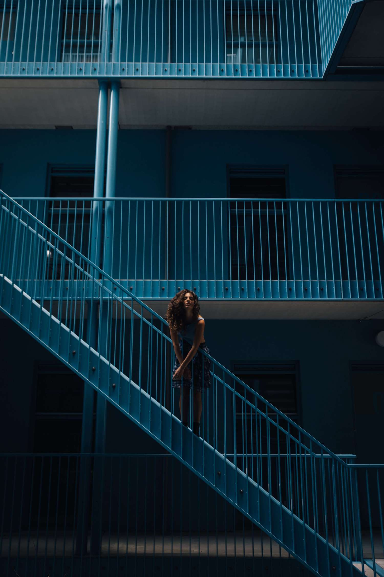 Model in a blue minimalistic building.