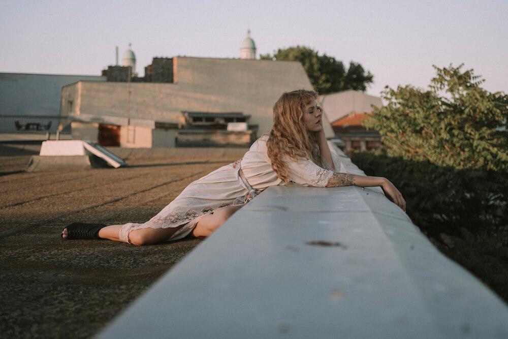 Portrait of girl on a rooftop in Berlin with sunlight boheme style by photographer Krystsina Shyla