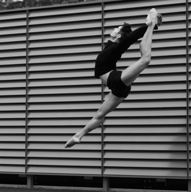 In black and white, a ballet dancer captured in the air.