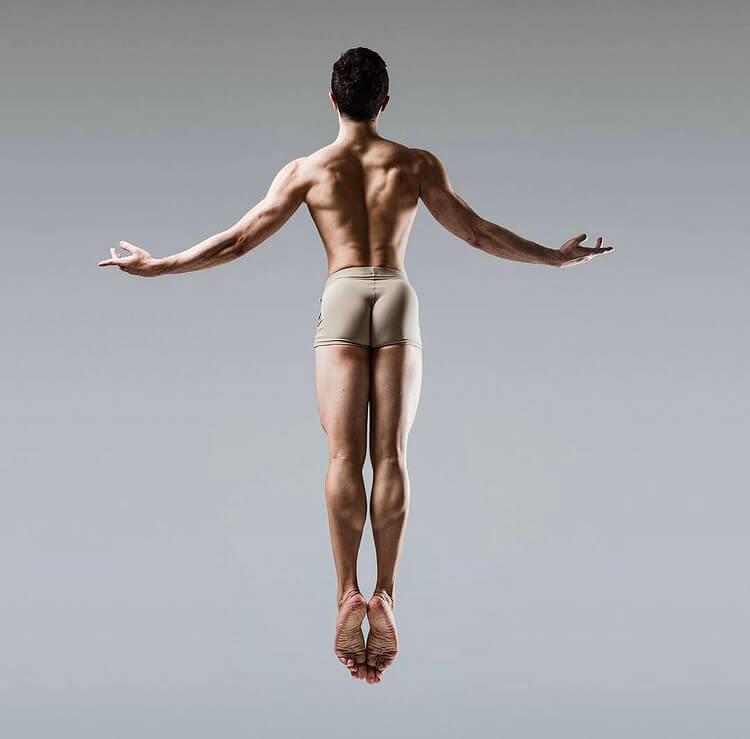 A male ballet dancer jumping backwards.