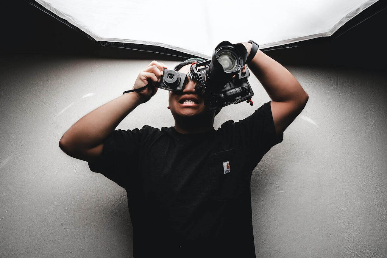 A photographer using two cameras at the same time.
