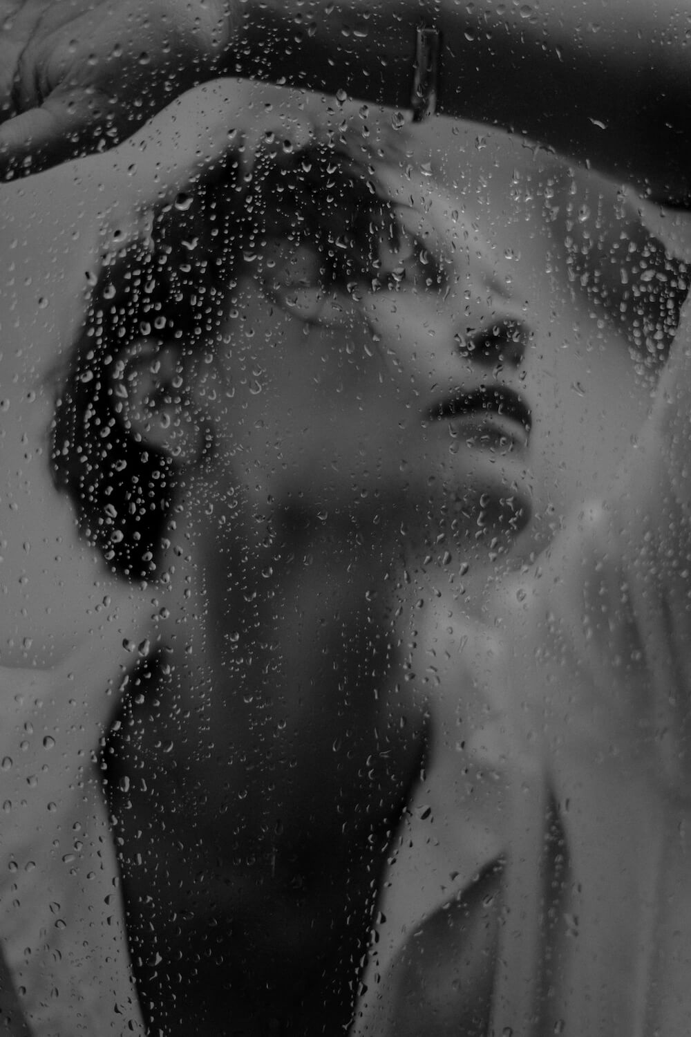 Portrait through a window with rain drops in back and white by photographer Krystsina Shyla