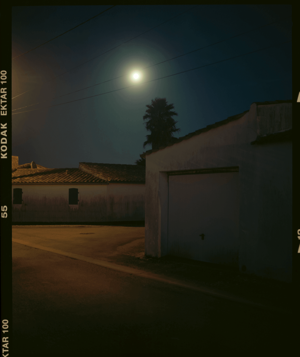 Photograph taken with an analogue camera of a village at night.