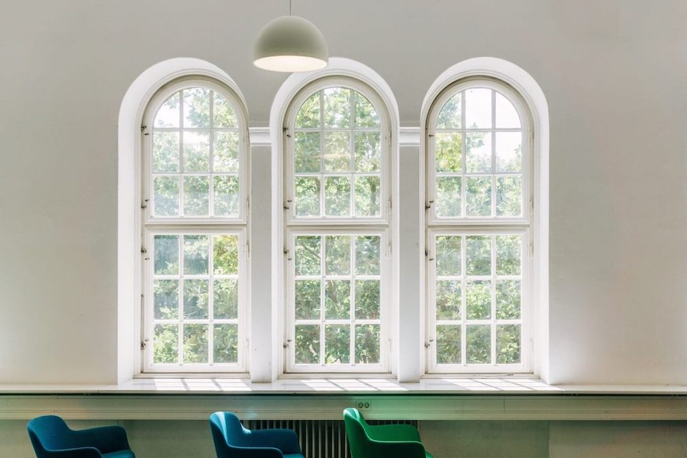 Interior of a bright room with three large windows.