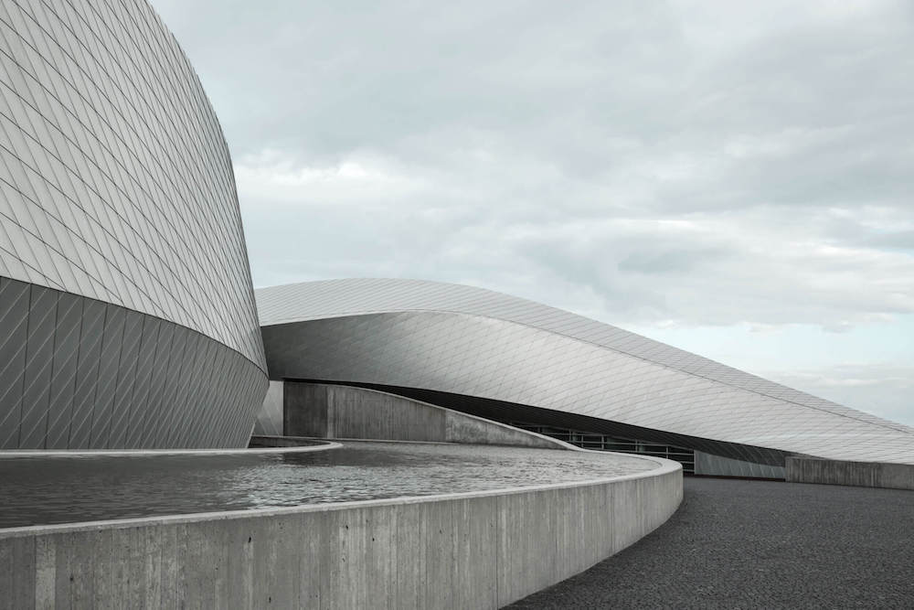 Curved building with an artificial pond.