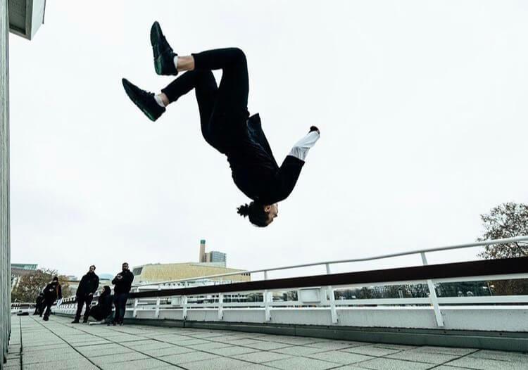 An urban dancer doing a parkour jump.