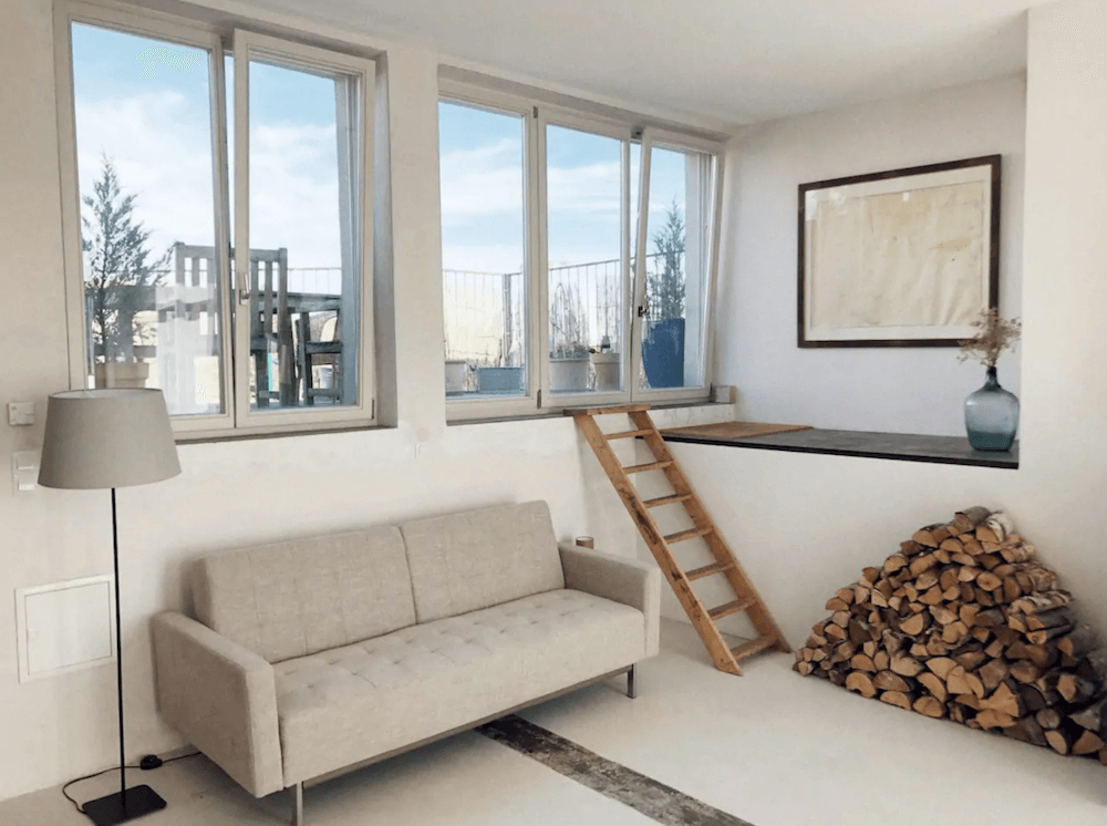 Artist loft living room with fireplace available for rent for your next film production in Berlin, Germany. Minimalist and unique interior design