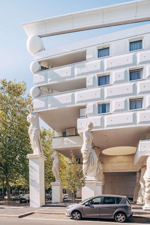 Facade of a white Romanesque building, with sculptural columns.