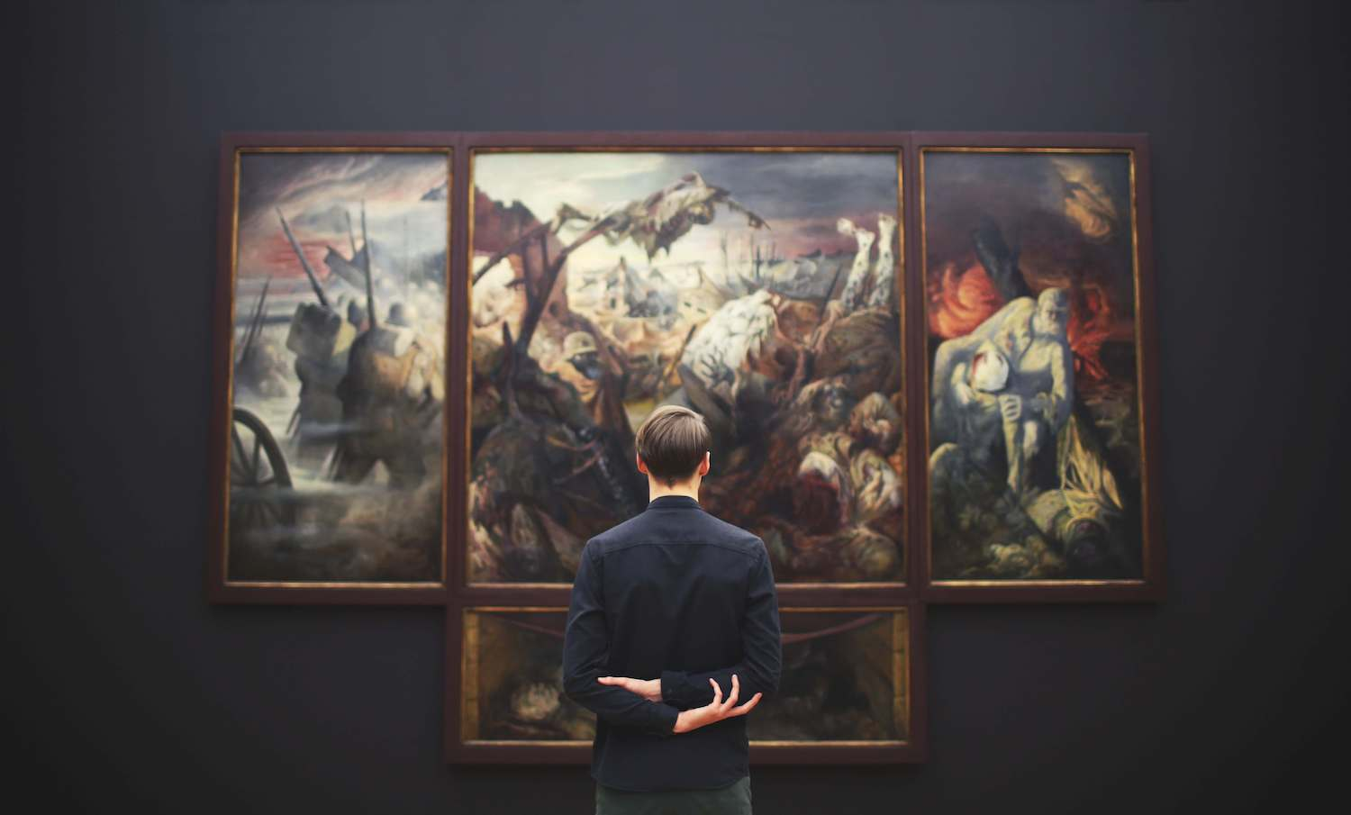 A man contemplating a picture in a museum.