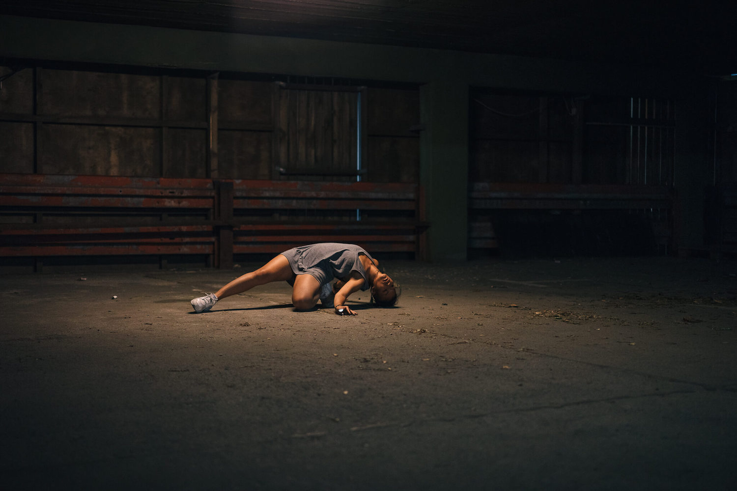 A girl dancing on the ground in the middle of a dark empty street.
