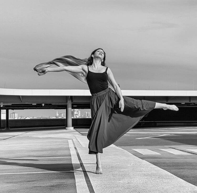 A dancer in motion in an empty car park.