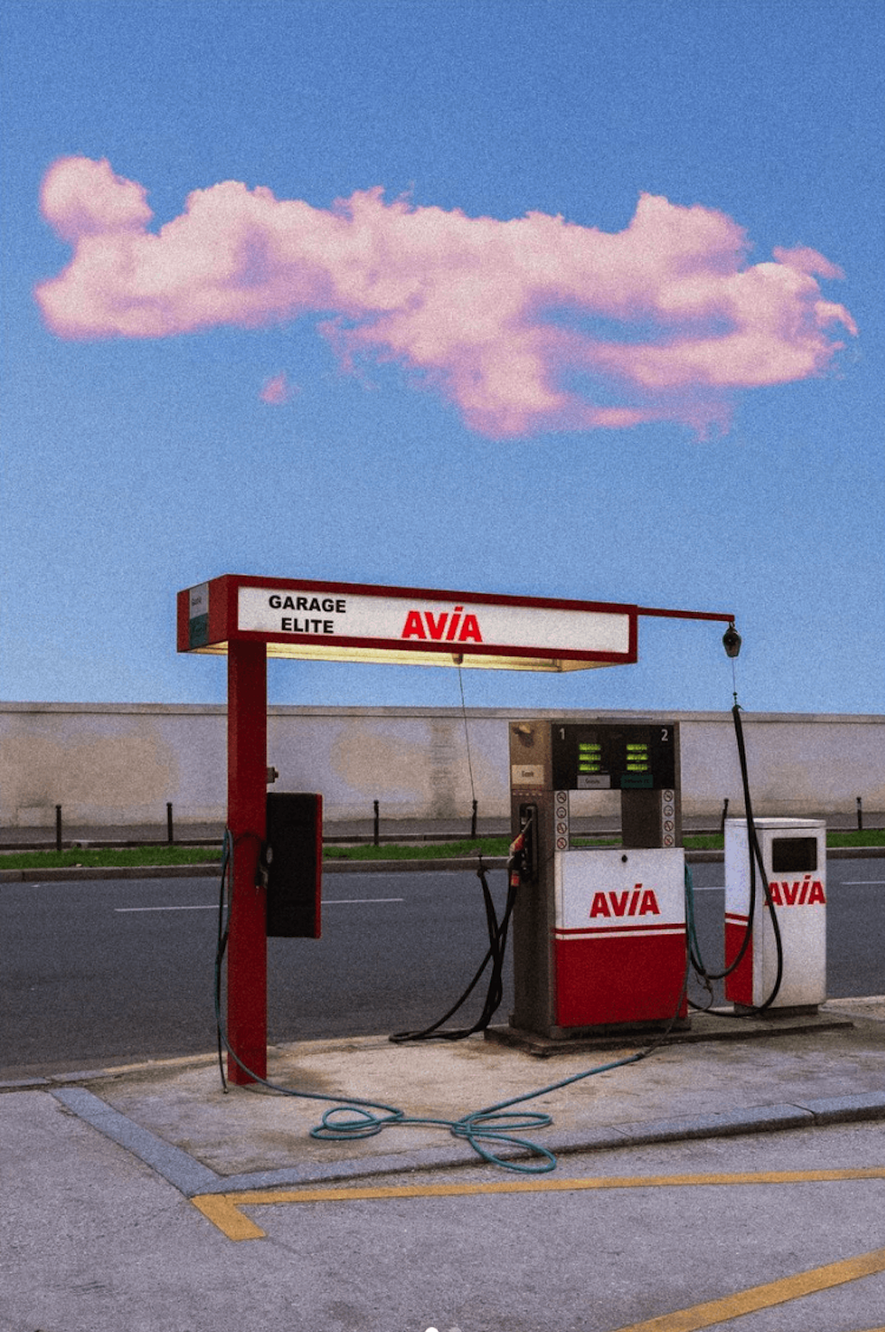 A petrol station in the middle of an empty road.