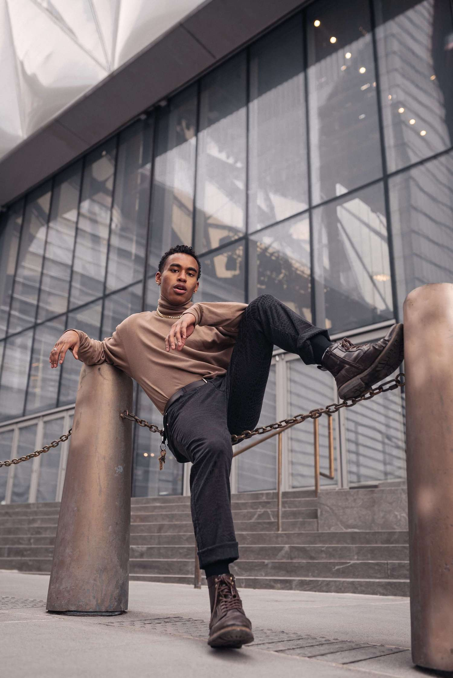 Male model sitting on a chain, glass building on the background.