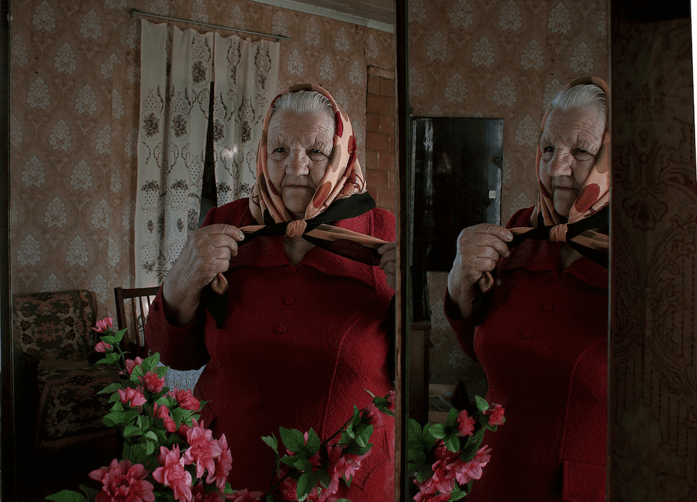 Portrait of grand mother with scarf in front of a mirror in Belarus by photographer Krystsina Shyla