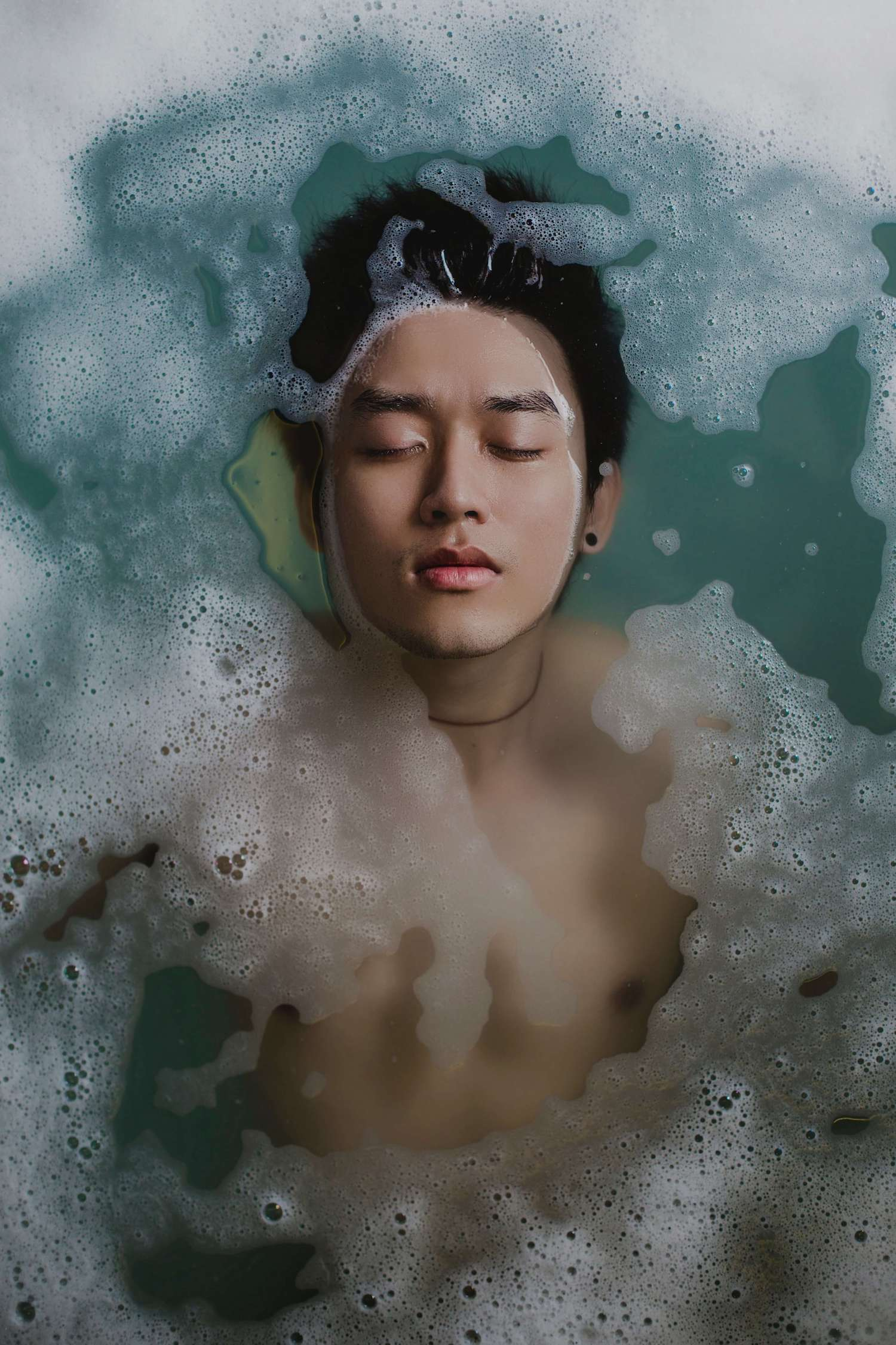 A young man in a foaming bath.
