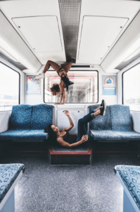 Two girls dancing and doing acrobatics inside the Sbahn.
