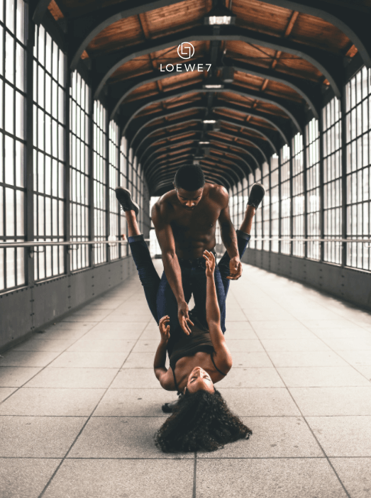A couple dancing in a train station.