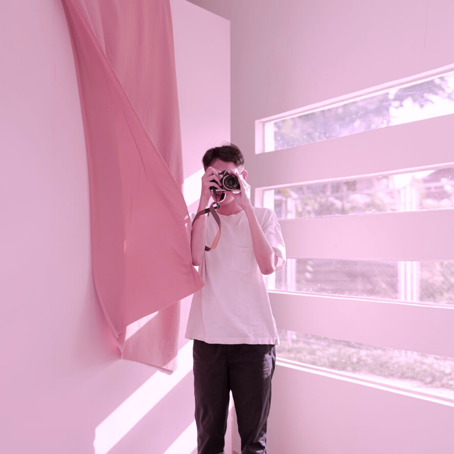 Book a photographer with Beazy - photographer making photos in a pink background