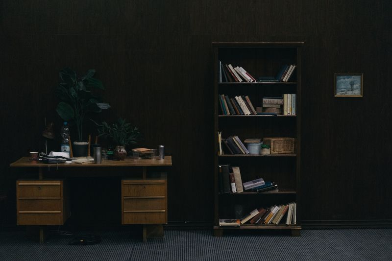 Dark themed library and office desk, set design by John Laing, Set designer on Beazy