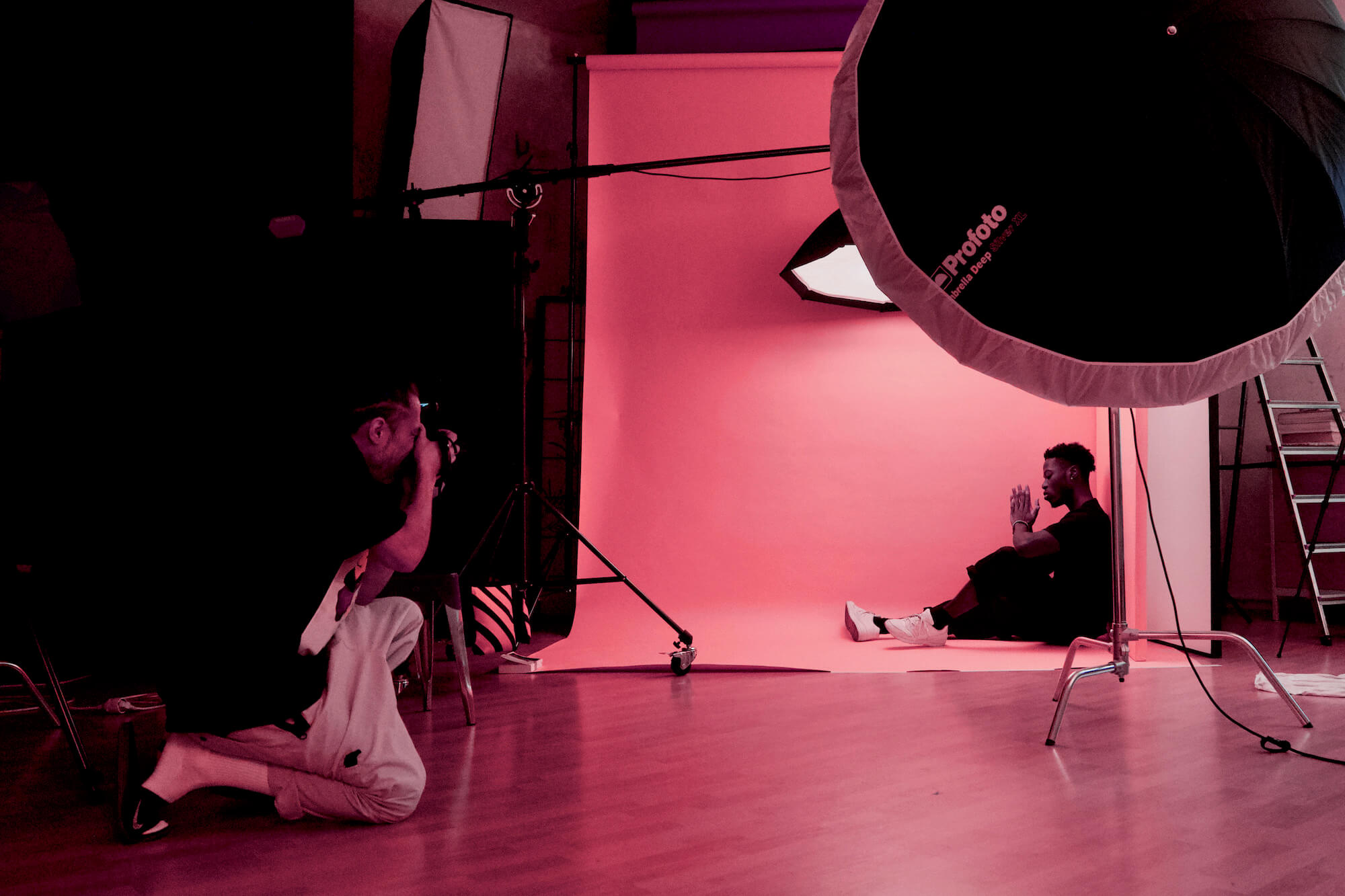 Photoshoot for a jewellery brand, black model in a pink background in a professional photo studio.