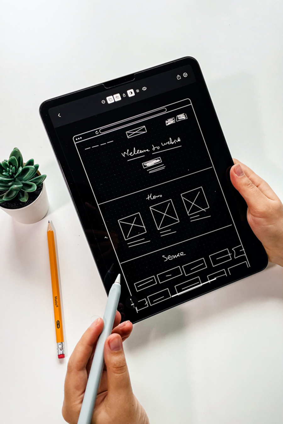 Person holding a tablet while creating a websites wireframe