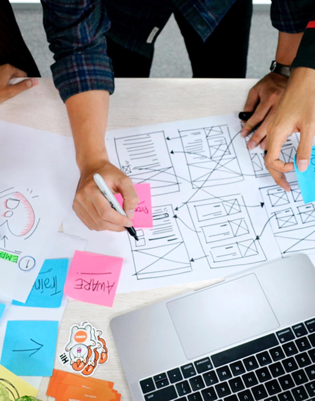 Multiple people working on a websites UX frames