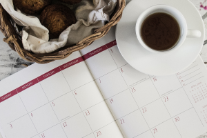 Full cup of tea sitting on an open calendar, nect to a wicker basket full of bread rolls.