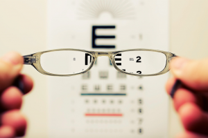 Medicare doesn't cover vision exams. Person holding glasses in front of a blurry eye exam.