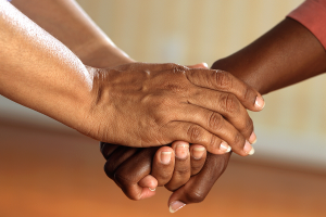 Care taker holding their senior patients hands.