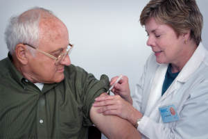 Elderly man getting vaccine in his arm from woman doctor.
